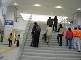 駅の正面階段を上る視覚障害者と付き添いの人達