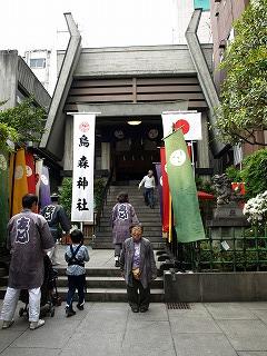 高いビルに囲まれた烏森神社の前で記念撮影