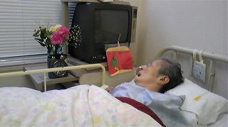 母の枕元にきれいな花と絵手紙が