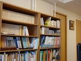 机の後ろの3つの本棚と本