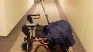 歩行器の荷物かごに念入りにカバーをかぶせ杖もいれて出発