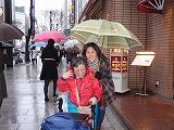 雨の中銀座の通りを歩行器を押している所