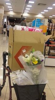 歩行器の椅子の部分に食料品をつめた段ボール箱を置いて