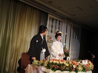 紋付きと白無垢の打ち掛け姿でひな壇に並ぶ新郎新婦