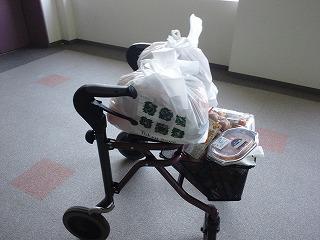買い込んだ食料を歩行器に積み上げているところ