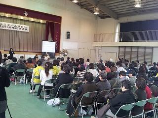 記念式典で講演をする私と140人を超える受講者