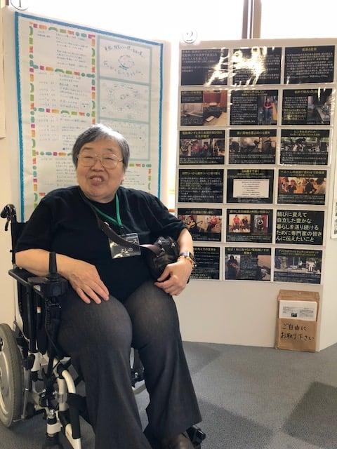 電動車いすに乗って自分のポスターの前で記念撮影