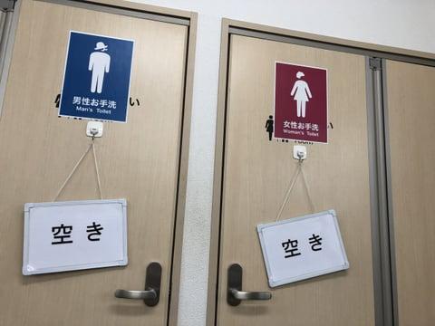 トイレのドアが左右に2つ並んだ写真。男女の別が大きなマークで示されており、それぞれ「空き」と大きく印刷された札が下がっている。